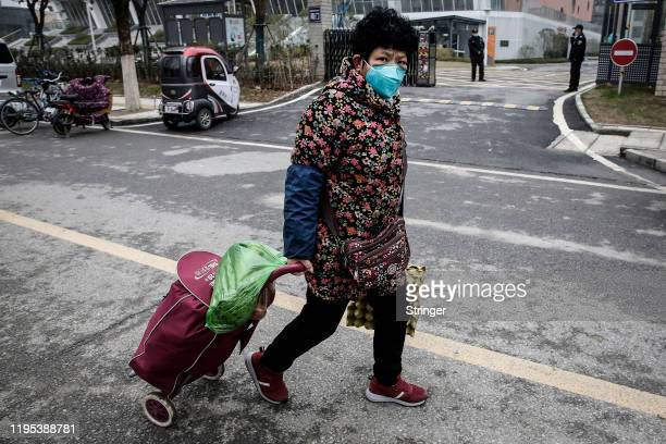 A resident wear masks to buy vegetables in the market on January 23th2020 in Wuhan Hubei£¬China Flights trains and public transport including buses...
