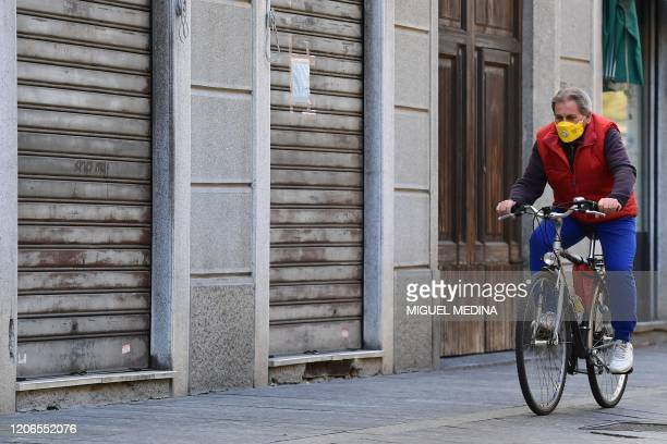 Resident wearing a protective mask rides a bicycle past closed shops in a deserted street of central Codogno, southeast of Milan, on March 11, 2020 a...