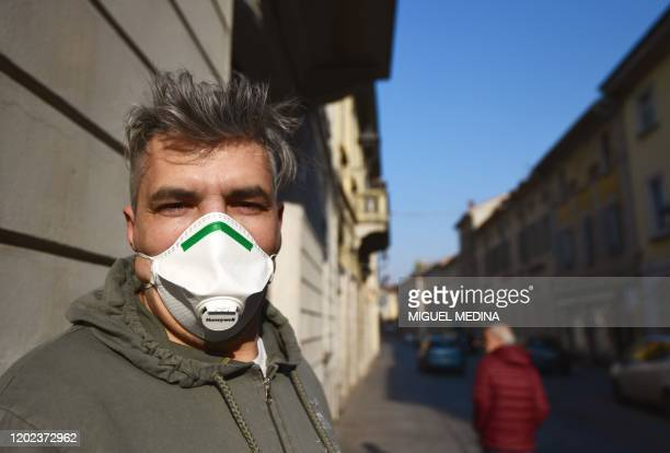 A resident wearing a protective respiratory mask looks on in a street of Codogno southeast of Milan on February 22 2020 An Italian man became the...