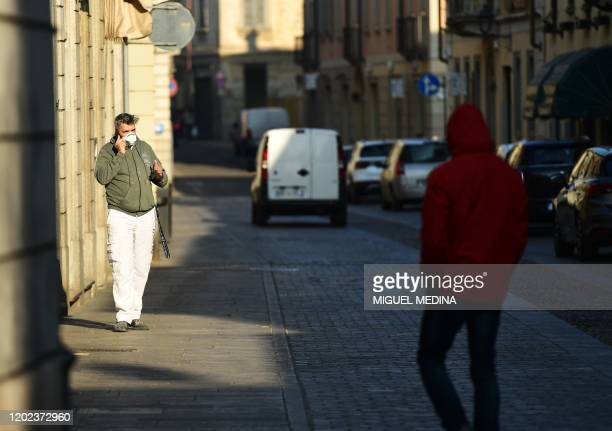 A resident wearing a protective respiratory mask speaks on his mobile phone in a street of Codogno southeast of Milan on February 22 2020 An Italian...