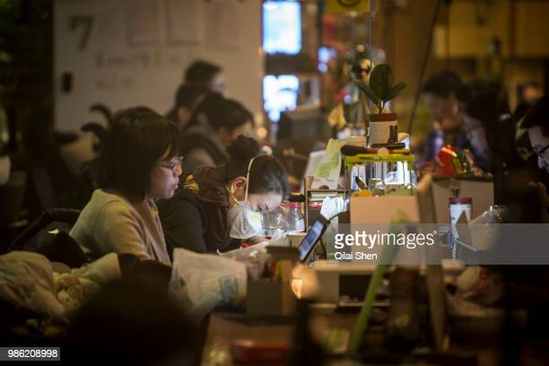 A resident wears a face mask while working at her station inside a You community in Beijing China on Monday Nov 30 2015 Nearly 5000 people across...