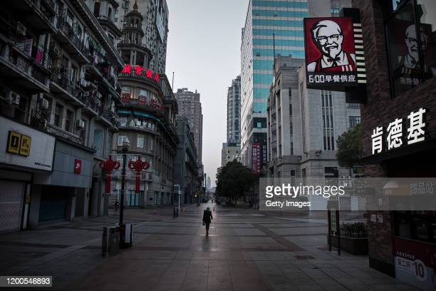 A resident wears a protective mask as she walk on an empty business street on February 13 2020 in Wuhan Hubei province China Flights trains and...