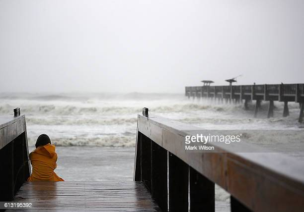 Resident Wendy Bishop watches as large waves pound the Jacksonville Pier October 7 2016 in Jacksonville Beach Florida Hurricane Matthew passed by...