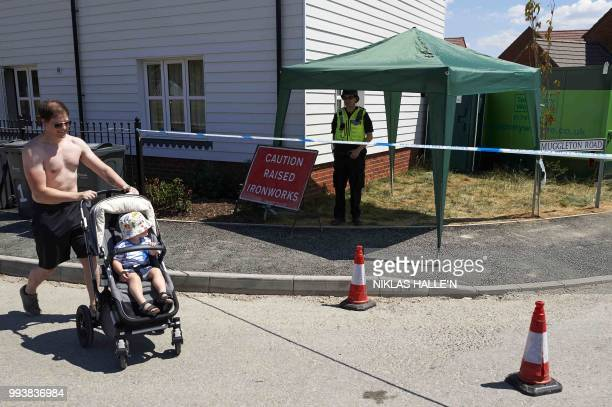A resident wheels a pram past police officers standing guard at a residential house in Amesbury southern England on July 8 2018 The exposure of an...