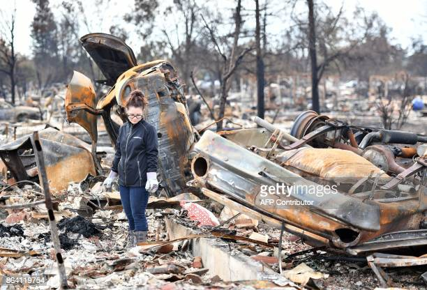 A resident who declined to give her name walks near flipped cars at her burned property in Santa Rosa California on October 20 2017 Residents are...