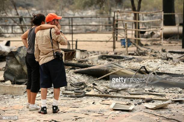 A resident who would only give his name as Adi is consoled by a friend as he sees the charred remains of his home that was burned by the Station Fire...