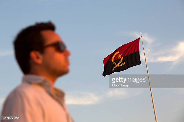 A resident worker stands beneath an Angolan national flag flying at the Army Fort Museum in Luanda Angola on Friday Nov 8 2013 Angola the largest...