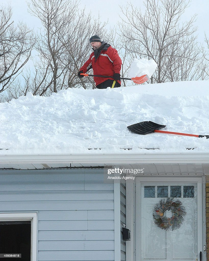 A resident works to clear snow from the roof on November 21, 2014 in Buffalo, New York as the death toll attributed to Buffalo snow rises to 13. A brutal blast of Arctic air triggered a lake-effect storm and snow in the states of New York, Ohio, Michigan, Wisconsin and Pennsylvania.