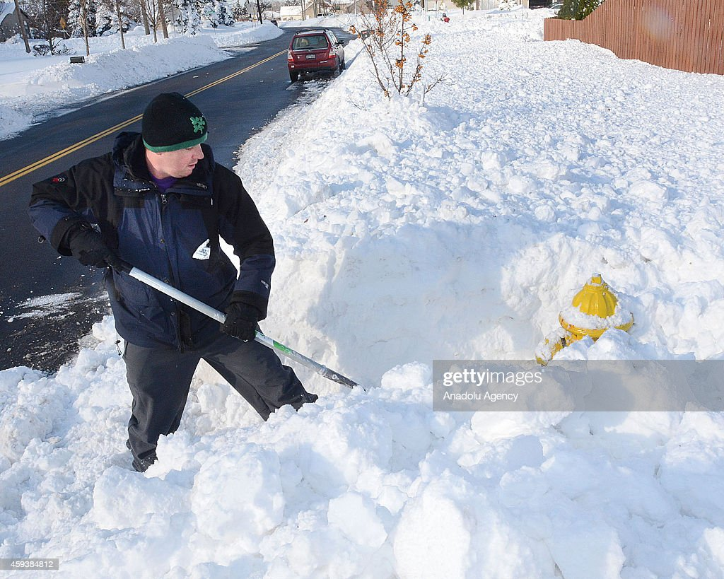 A resident works to clear snow on a roadside on November 21, 2014 in Buffalo, New York as the death toll attributed to Buffalo snow rises to 13. A brutal blast of Arctic air triggered a lake-effect storm and snow in the states of New York, Ohio, Michigan, Wisconsin and Pennsylvania.