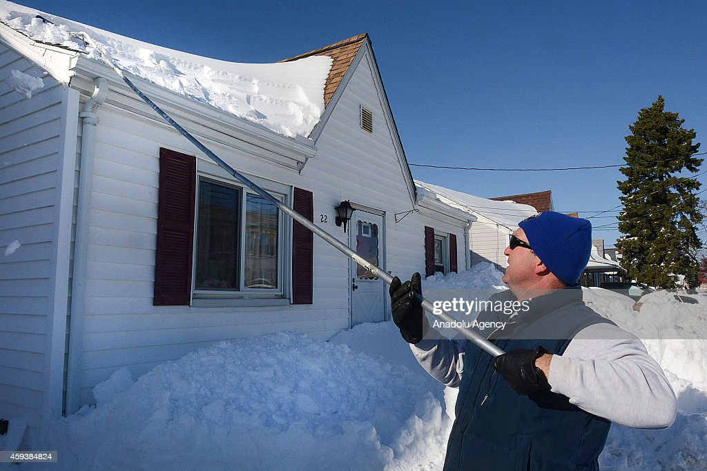 A resident works to remove snow from the roof on November 21, 2014 in Buffalo, New York as the death toll attributed to Buffalo snow rises to 13. A brutal blast of Arctic air triggered a lake-effect storm and snow in the states of New York, Ohio, Michigan, Wisconsin and Pennsylvania.