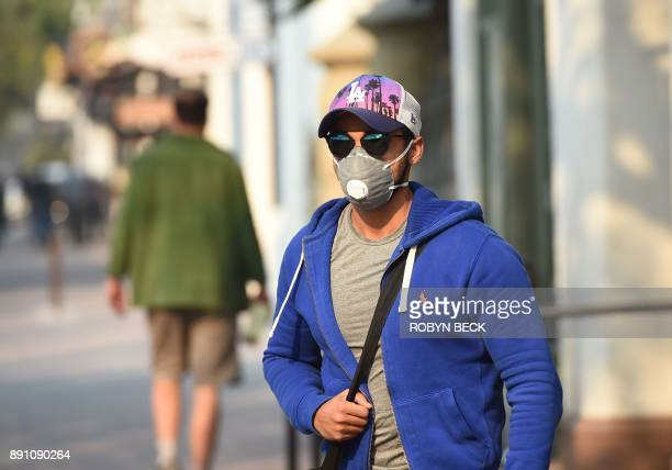 Resident Younis Gamal wears a face mask on State Street the main shopping street in Santa Barbara California December 12 2017 The Thomas Fire now the...