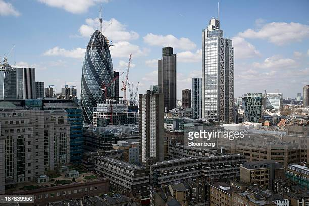 Residential and commercial properties stand in front of the Swiss Re building also known as 'the Gherkin' left Tower 42 center and the Heron Tower in...