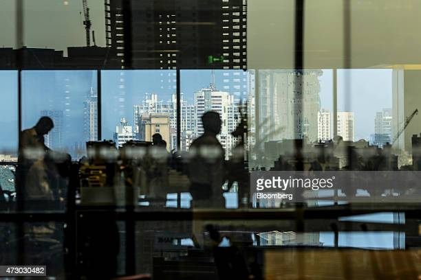 Residential and commercial towers are seen through and reflected on an office building in the Lower Parel area of Mumbai India on Monday May 11 2015...