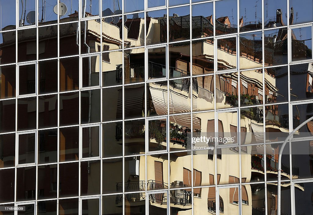 Residential apartment blocks are seen reflected in a building's windows in Rome, Italy, on Friday, July 26, 2013. Italy's home prices are low enough to trigger an increase in purchases for the first time since 2006, though that won't lift values for at least two years, according to the Nomisma institute. Photographer: Alessia Pierdomenico/Bloomberg via Getty Images