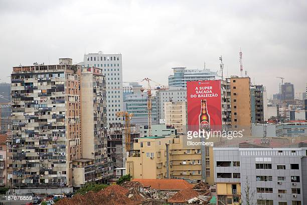 Residential apartment blocks stand beyond a billboard for Super Bock beer on the city skyline in central Luanda Angola on Friday Nov 8 2013 Angola...