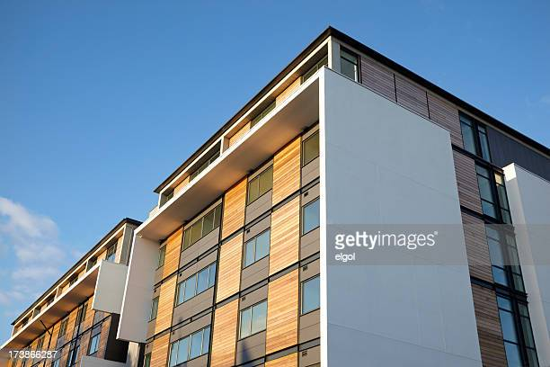 residential apartment with wood panels and blue clear sky - manchester uk stock photos and pictures