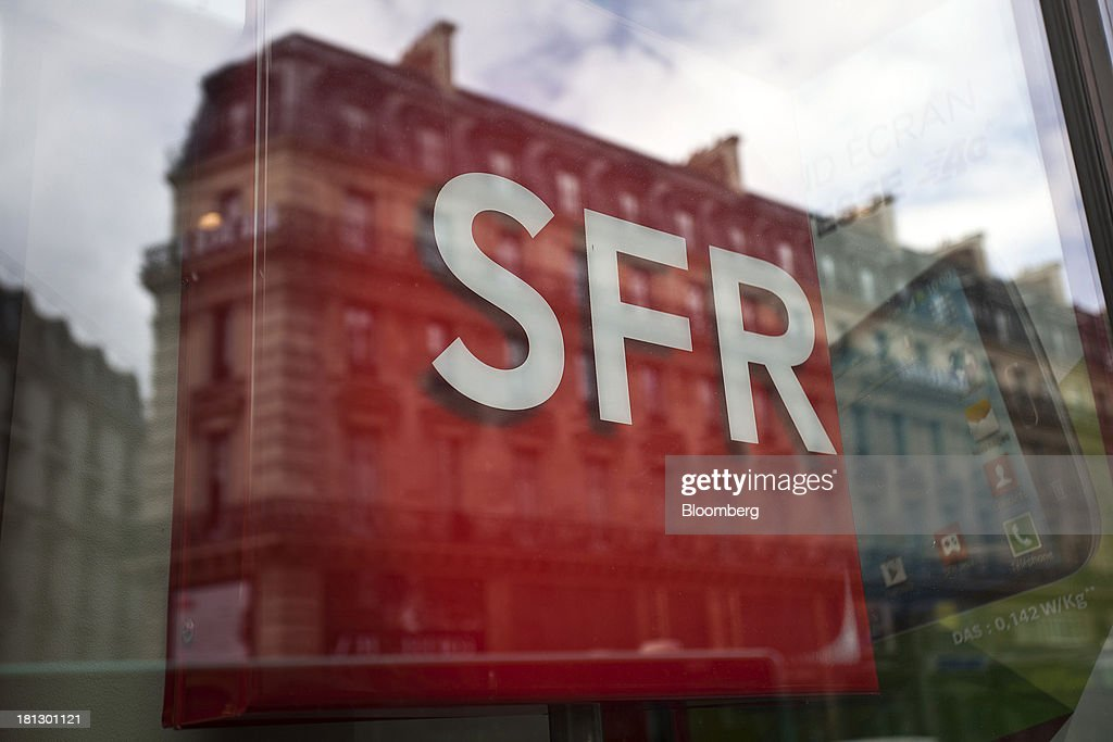 Residential apartments are reflected in the window of an SFR store, a mobile-phone unit of Vivendi SA, in Paris, France, on Thursday, Sept. 19, 2013. Bank of France General Council member Bernard Maris said France will end up restructuring its debt as tax 'optimization' by large companies including Google Inc. will leave too big a burden on the middle class. Photographer: Balint Porneczi/Bloomberg via Getty Images