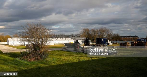 Residential apartments are seen on the horizon beyond the site of a temporary mortuary, during its construction in Manor Park, east London on April 2...