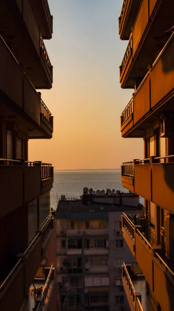 Residential Buildings By Sea Against Sky During Sunset