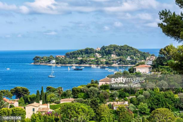 residential buildings by sea against sky - saint jean cap ferrat stock pictures, royalty-free photos & images
