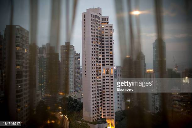 Residential buildings shot through a curtain stand in the Central district in Hong Kong China on Tuesday Oct 8 2013 Property market imbalances are...