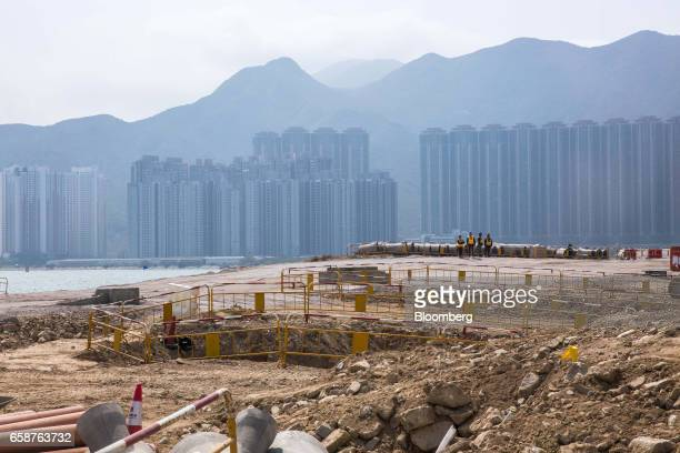 Residential buildings stand across the water from the construction site of the Hong KongZhuhaiMacau Bridge in Hong Kong China on Tuesday March 28...