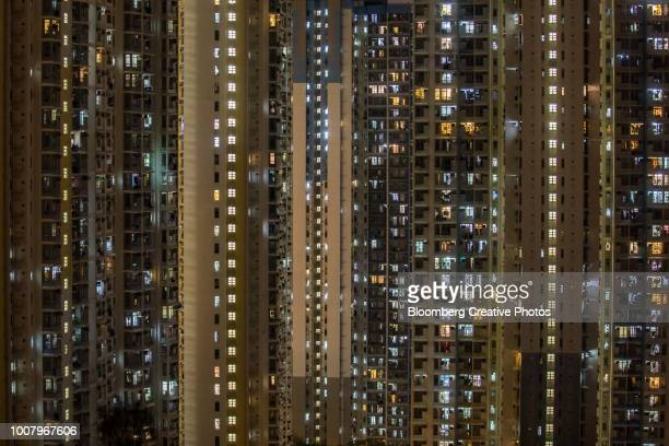 residential buildings stand illuminated in hong kong - hong kong stock pictures, royalty-free photos & images