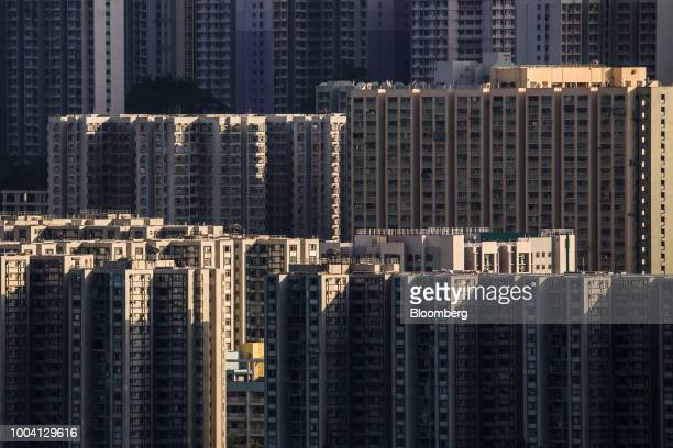 Cranes stand at a construction site at the former Kai Tak airport area in front of residential buildings in Hong Kong China on Saturday July 21 2018...