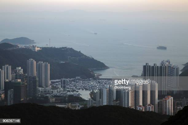 Residential buildings stand near boats moored in Aberdeen Harbor in the Aberdeen area of Hong Kong China on Monday Jan 15 2018 For the eighth year in...