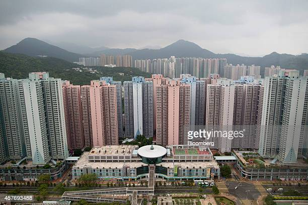 Residential buildings stand near hills in the Tseung Kwan O district of Hong Kong China on Thursday Oct 23 2014 Hong Kong is scheduled to release...
