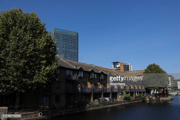 Residential houses stand in view of the Barclays Plc office headquarters office building in the Canary Wharf business financial and shopping district...