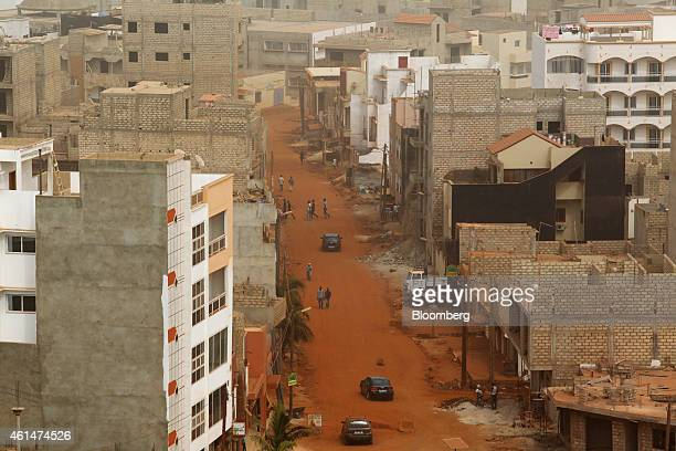 Residential housing and properties under construction stand alongside a dirt road in Dakar Senegal on Sunday Jan 11 2015 Dakar with 3 million...