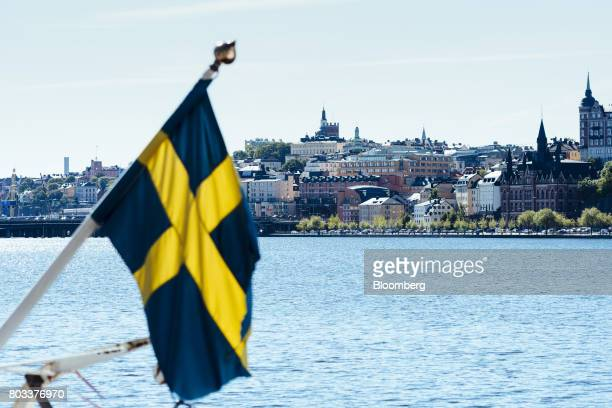 Residential housing blocks stand near the waterside beyond a Swedish national flag in the Soeder Maelarstrand area of Soedermalm in Stockholm Sweden...