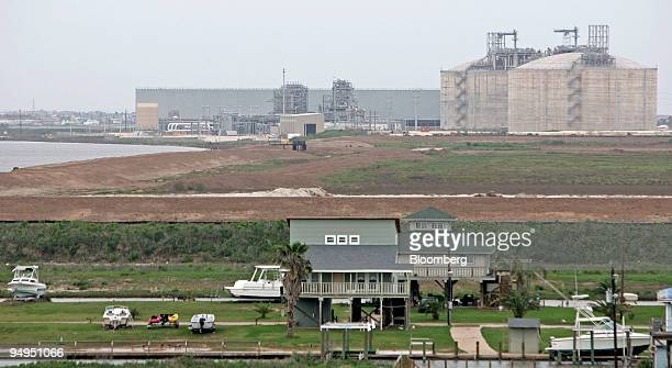 Residential housing stands near the Freeport LNG facility in Quintana Texas US on Wednesday April 1 2009 This facility boasts two gigantic LNG tanks...