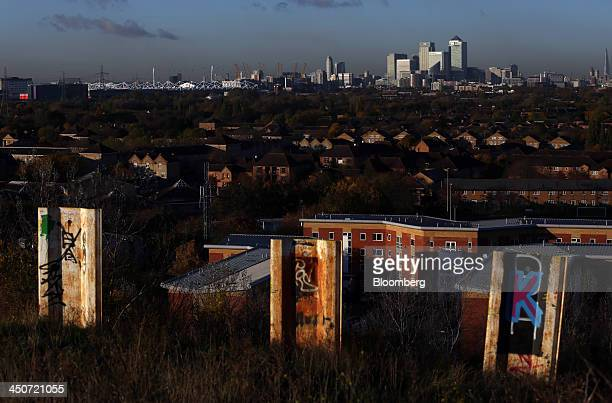 Residential properties stand against a backdrop of skyscrapers and bank headquarters in the Canary Wharf business and financial district of London UK...