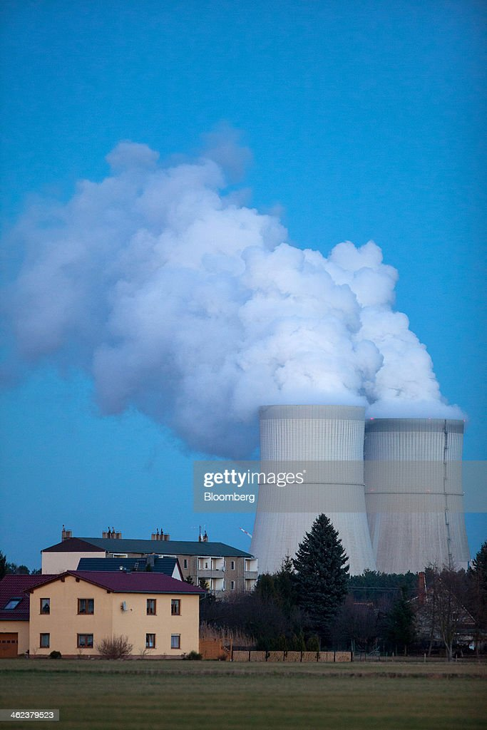 Residential property stands as vapor rises from the cooling towers of the Schwarze Pumpe lignite powered power plant, operated by Vattenfall AB, in Spremberg, Germany, on Saturday, Jan. 11, 2014. Across the continent's mining belt, from Germany to Poland and the Czech Republic, utilities such as Vattenfall AB, CEZ AS and PGE SA are expanding open-pit mines that produce lignite. Photographer: Krisztian Bocsi/Bloomberg via Getty Images