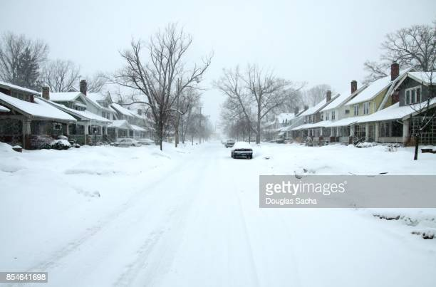 residential street covered in a blanket of snow after the storm - winter weather stock photos and pictures