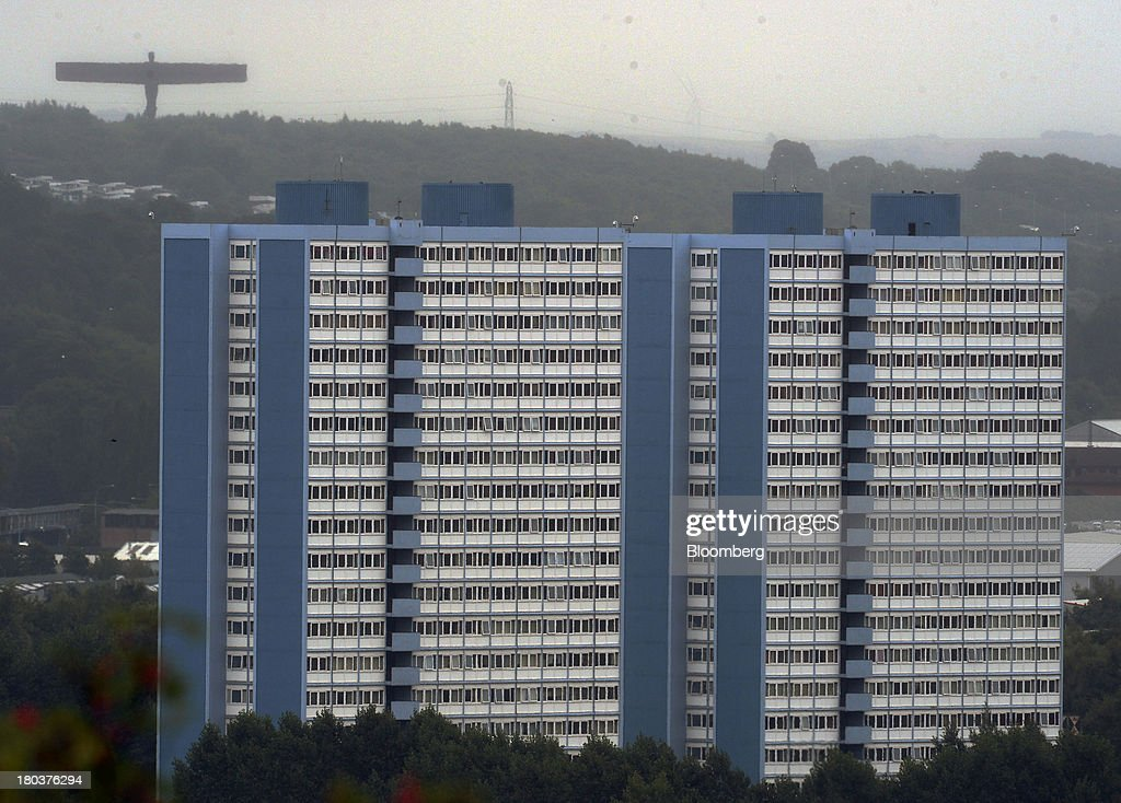 A residential tower block stands as sculpture the ''Angel of the North,'' is seen on the horizon in Newcastle-upon-Tyne, U.K., on Wednesday, Sept. 11, 2013. U.K. house prices rose for a seventh month in August and will probably continue to increase through the rest of the year, according to a report by Halifax. Photographer: Nigel Roddis/Bloomberg via Getty Images