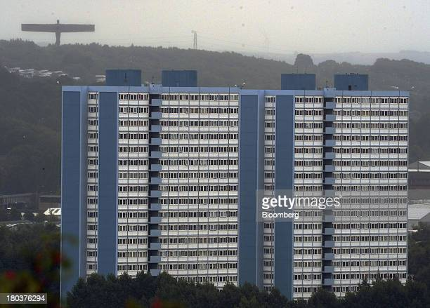 A residential tower block stands as sculpture the ''Angel of the North'' is seen on the horizon in NewcastleuponTyne UK on Wednesday Sept 11 2013 UK...