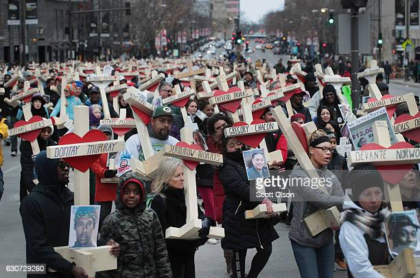 Residents, activists, and friends and family members of victims of gun violence march down Michigan Avenue carrying nearly 800 wooden crosses bearing...