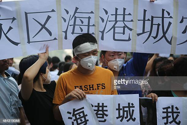 Residents affected by the explosions that hit a nearby chemical warehouse last week hold banners and placards as they join a protest outside the...