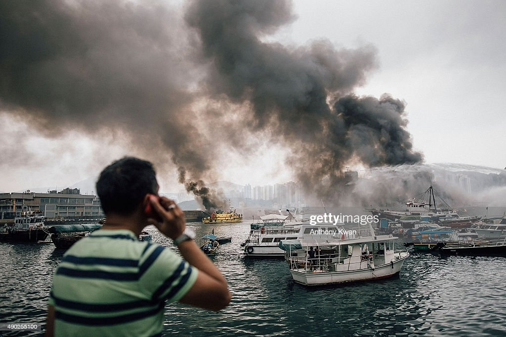 Residents and bystanders watch as firefighters extinguish fires on boats at the Shau Kei Wan typhoon shelter on September 27, 2015 in Hong Kong. A fire swept through several boats anchored at the Shau Kei Wan typhoon shelter.