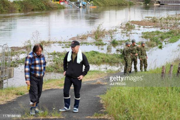 Residents and military personals come to see the flooded river after heavy rains in Sakura city Chiba prefecture on October 26 2019 Four people were...