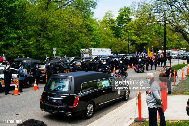 Residents and police officers pay their respects to Glen Ridge Police Officer Charles Roberts during his funeral after he passed away from the...