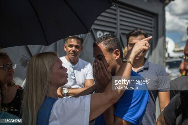 Residents and relatives mourn the loss of friends and relatives at the scene of a shooting at Raul Brazil School on March 13, 2019 in Suzano, Brazil....