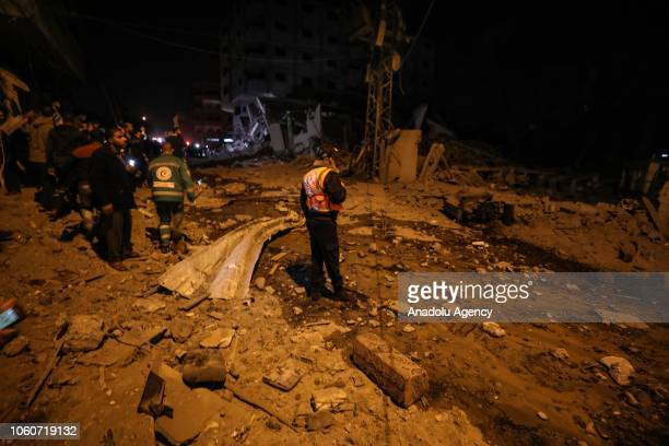 Residents and rescue teams inspect the damage after the Israeli airstrikes hit the Hamasrun AlAqsa TV in Gaza on November 12 2018