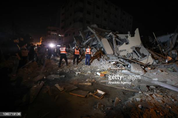 Residents and rescue teams inspect the destroyed building after the Israeli airstrikes hit the Hamasrun AlAqsa TV in Gaza on November 12 2018