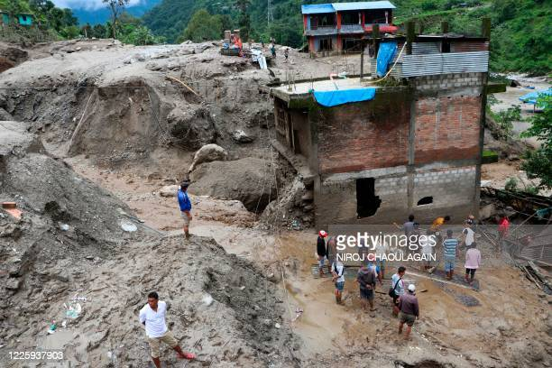 TOPSHOT Residents and rescue workers inspect the area outside a house damaged by a landslide and the swell of the ThadoKoshi river due to heavy rains...