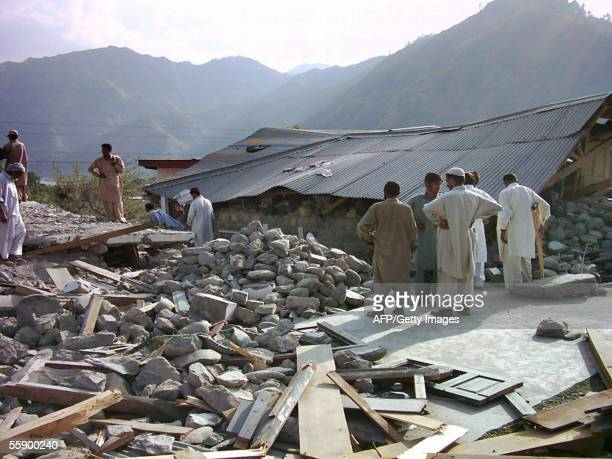 Residents and rescue workers look at what remains of a government girls' school in the town of Gari Habihullah 10 kms from Balakot 10 October 2005...