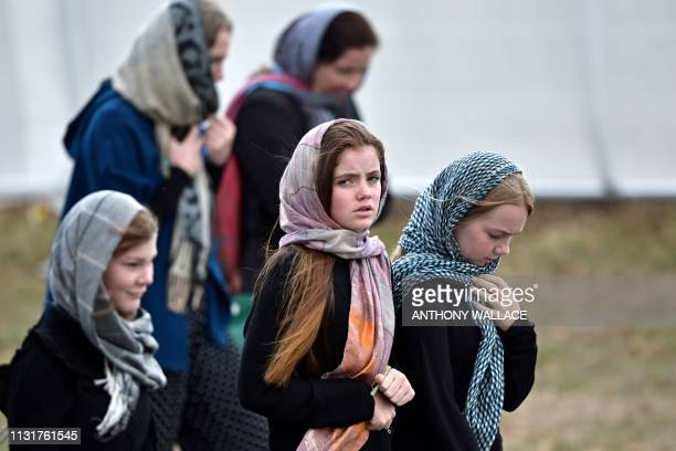 Residents and schoolchildren wearing headscarves arrive for the funeral of those killed in New Zealand's twin mosque attacks at Memorial Park...